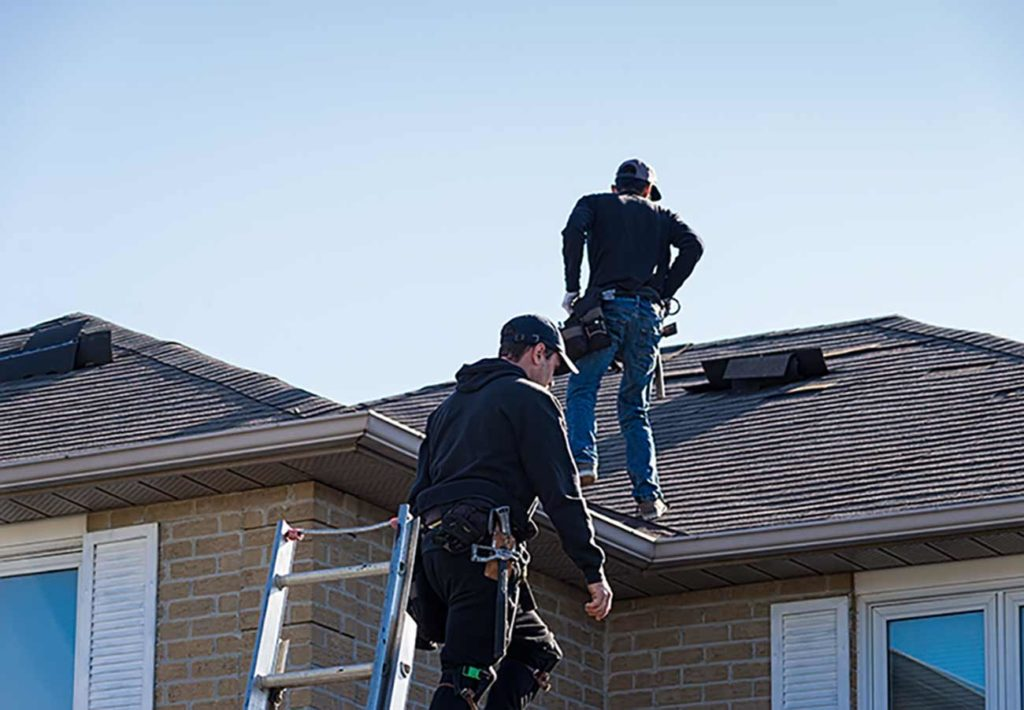 2 roofers walk on a roof